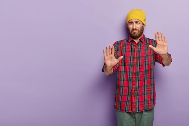 L'uomo triste e insoddisfatto mostra un segno di rifiuto, tiene i palmi aperti, dice di lasciarmi in pace, indossa un cappello giallo e una camicia a scacchi, ha un'espressione del viso disgustata Foto Gratuite