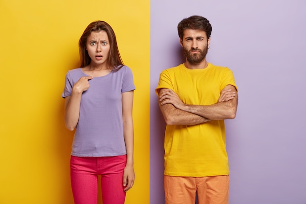 Dissatisfied sullen unshaven guy keeps arms folded, indignant young woman points at herself Free Photo