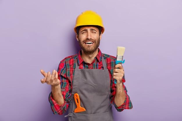Il pittore maschio insoddisfatto e infelice tiene in mano il pennello, temendo di avere molto lavoro, impegnato con le riparazioni a casa, indossa l'elmetto giallo e il grembiule grigio. operaio edile posa con strumenti di costruzione Foto Gratuite