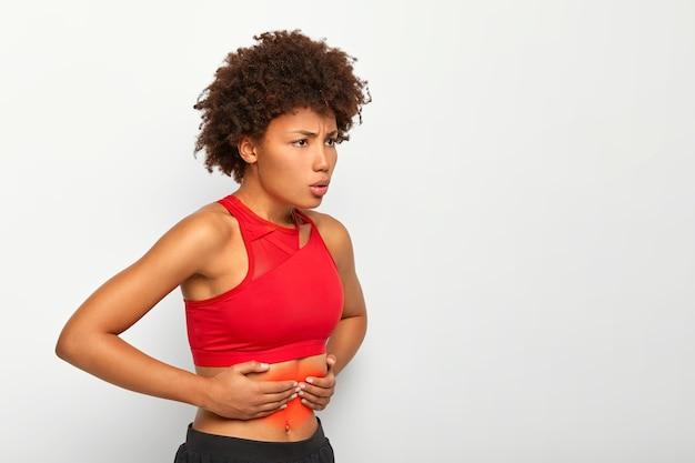 불만족스러운 여성은 배가 아프고, 배를 만지며, 심호흡을하며, 건강에 문제가 있으며, 달리기 또는 운동 후 질식을 겪습니다. 무료 사진