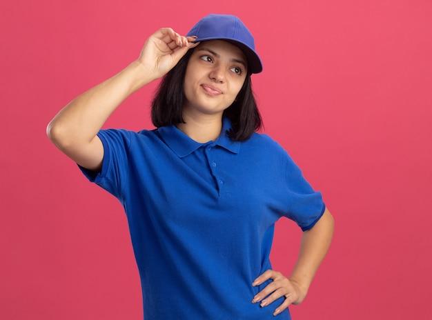 Giovane ragazza insoddisfatta delle consegne in uniforme blu e cappuccio che osserva da parte in piedi perplesso sopra il muro rosa Foto Gratuite