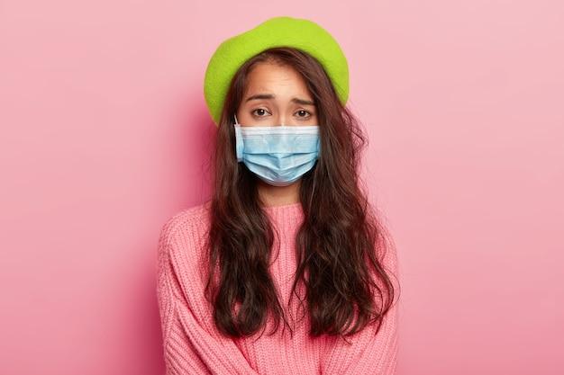 불만족스러운 젊은 여성 모델이 의료용 마스크를 쓰고, 중병에 걸렸고, 병원에 와서 의사를 만나고, 바이러스에 감염되었으며, 녹색 베레모와 점퍼를 착용했습니다. 무료 사진
