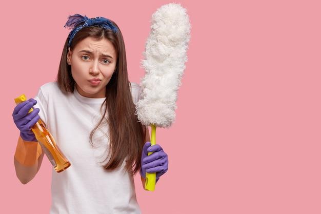 Недовольная девушка недовольно хмурится, несет банку с моющим средством и щетку, носит резиновые перчатки, устала от работы по дому. Бесплатные Фотографии