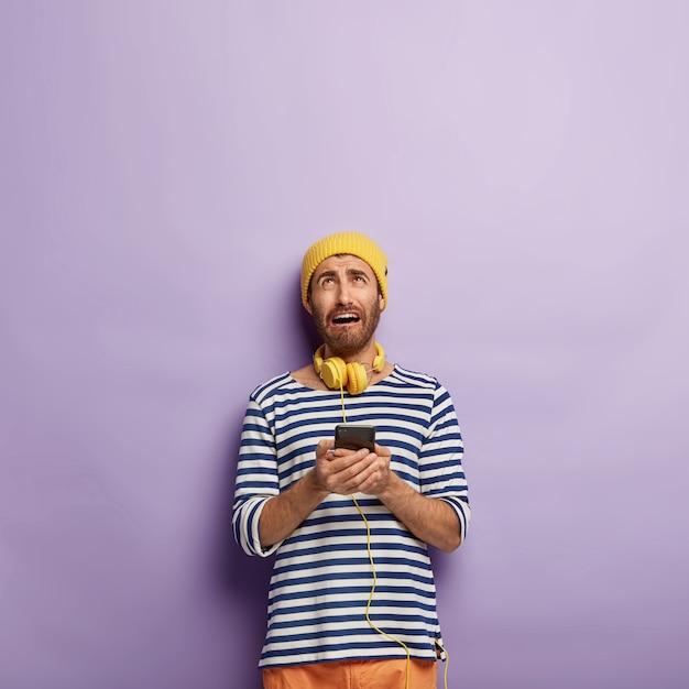 불만족스러운 젊은이가 현대 스마트 폰을 들고 비참한 표정으로 위를 보며 인터넷에 연결할 수 없습니다. 무료 사진