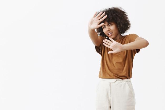 Giovane donna afroamericana dispiaciuta infastidita e incazzata con acconciatura afro che protegge dalla luce intensa con i palmi sollevati che coprono il viso e aggrottando le sopracciglia dal disagio Foto Gratuite