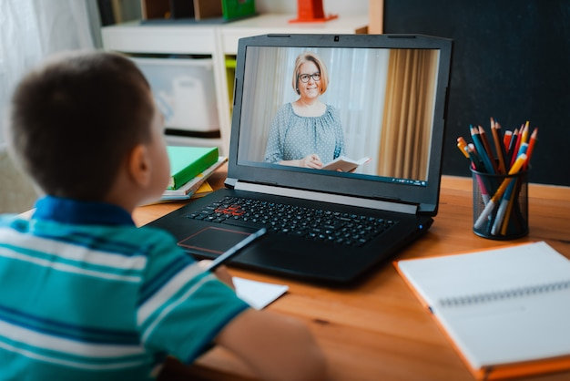 Distance learning online education. a schoolboy boy studies at home and does school homework. a home distance learning Premium Photo