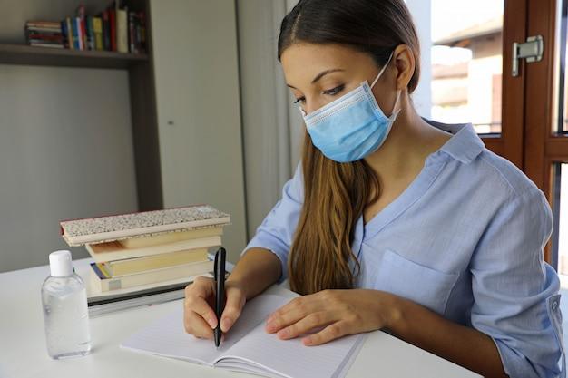 自宅でウイルス病2019-ncovについて勉強している遠隔学習検疫の若い女性。 Premium写真