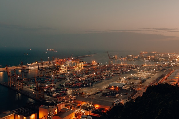 Distant shot of a port with boats loaded with cargo and shipment during nighttime Free Photo