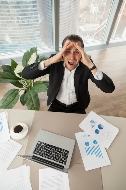 Distraught businessman at work looking up Free Photo