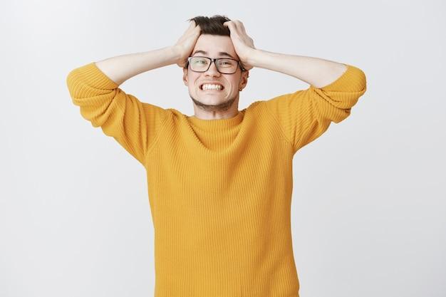 Обеспокоенный парень в панике трясет волосами и выглядит встревоженным Бесплатные Фотографии