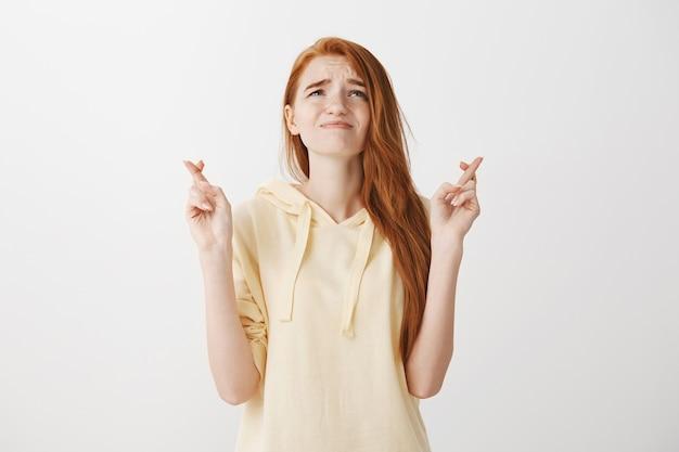 Обеспокоенная, обнадеживающая рыжая женщина умоляет бога, скрестив пальцы, удачи и в отчаянии смотрит вверх Бесплатные Фотографии