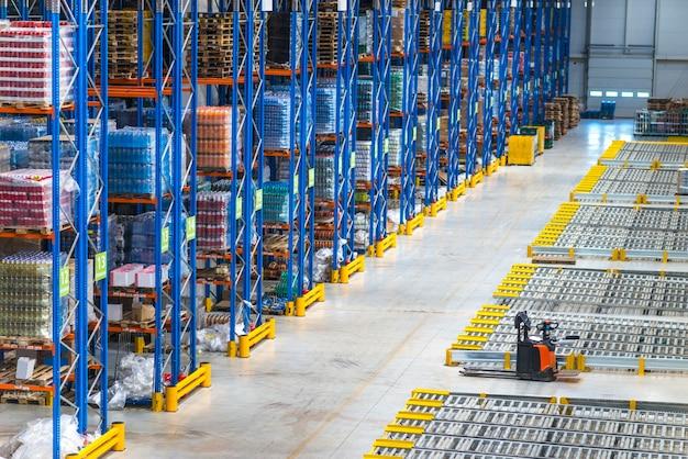 流通倉庫の建物の内部と棚に商品がある大きな保管エリア 無料写真