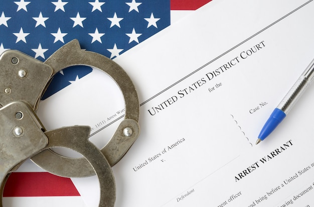 District court arrest warrant court papers with handcuffs and blue pen on united states flag. concept of permission to arrest suspect Premium Photo