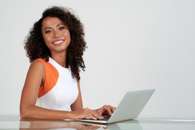 Макрофотография красивая женщина, ditting на стол с ноутбуком, улыбка на камеру Бесплатные Фотографии