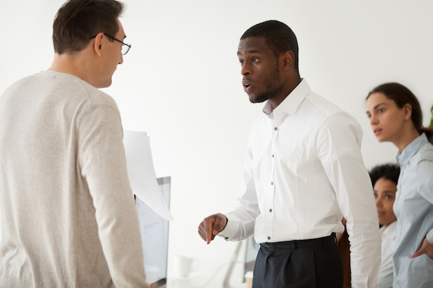 Diverse black employee and white boss arguing at work Free Photo