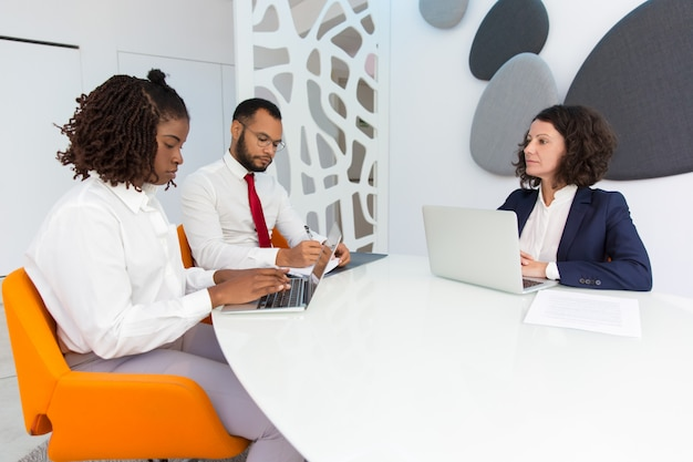 Diverse business colleagues reporting to female boss Free Photo