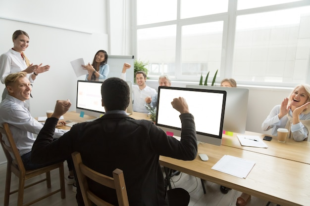 Diverse colleagues congratulating black coworker with good result or win Free Photo