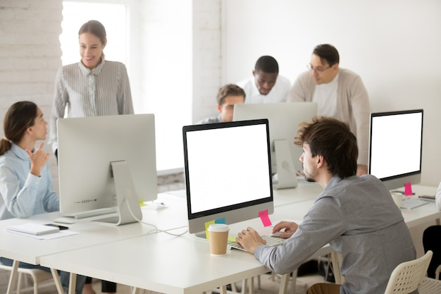 Diverse corporate employees group working together using computers in office Free Photo