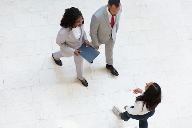 Diverse coworkers meeting in office hallway Free Photo