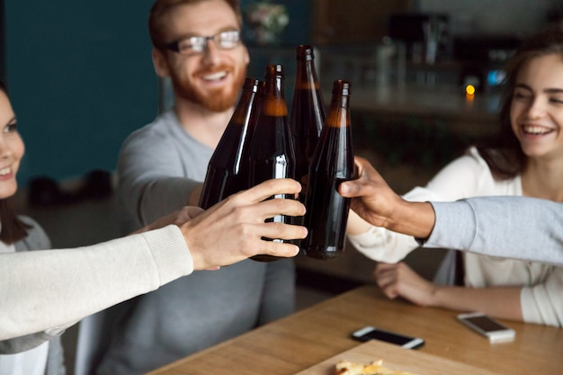 Diverse friends clinking craft beer bottles in pub, cheers concept Free Photo