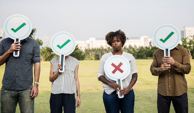 Diverse friends holding checkmark icons Free Photo