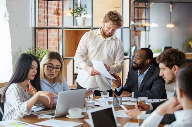 Diverse group of co-workers having casual discussion in office Free Photo