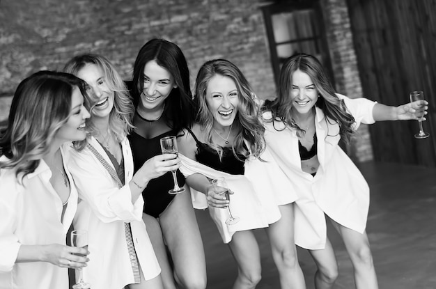 Diverse group of female friends enjoying at a party and laughing. group of beautiful  happy women having fun  in white clothes Premium Photo