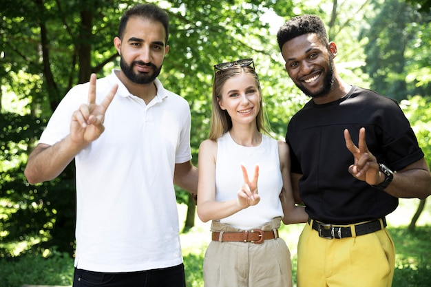Diverse group of friends doing peace sign Free Photo