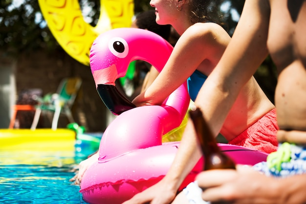 A diverse group of friends enjoying summer time by the pool with inflatable floats Free Photo