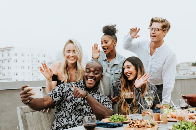Diverse group of friends taking a selfie at a rooftop party Premium Photo