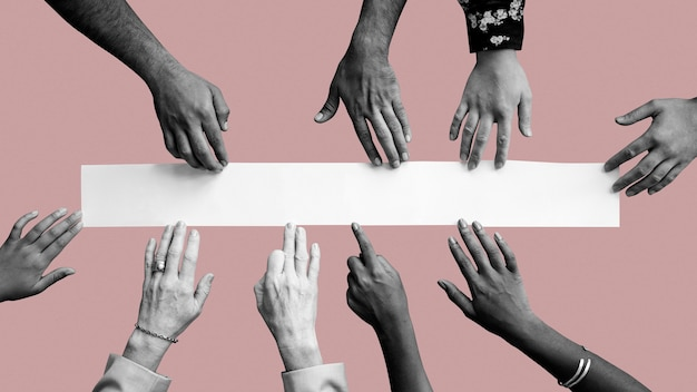 Diverse hands touching white paper mockup pink wallpaper Free Photo