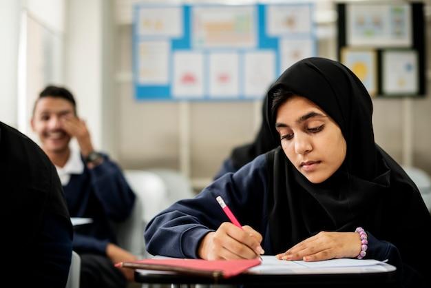 Diverse muslim children studying in classroom Premium Photo