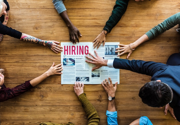 Diverse people hands reach out for hiring newspaper announcement Premium Photo
