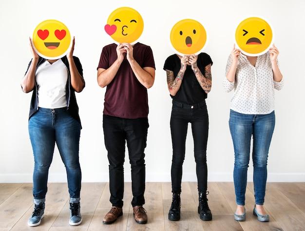 Diverse people holding emoticon Premium Photo