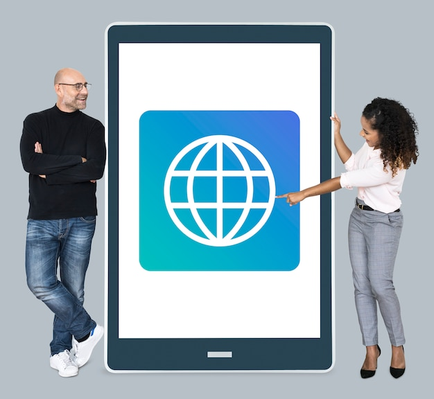 Diverse  people standing beside a tablet with www icon Free Photo