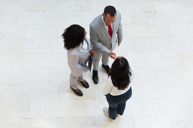 Diverse successful partners greeting each other Free Photo