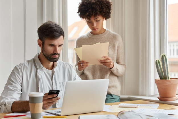 Diverse team of employees have informal meeting at domestic atmosphere, work with paper documents, develop startup during briefing. focused serious male ceo holds cell phone checks email box on laptop Free Photo