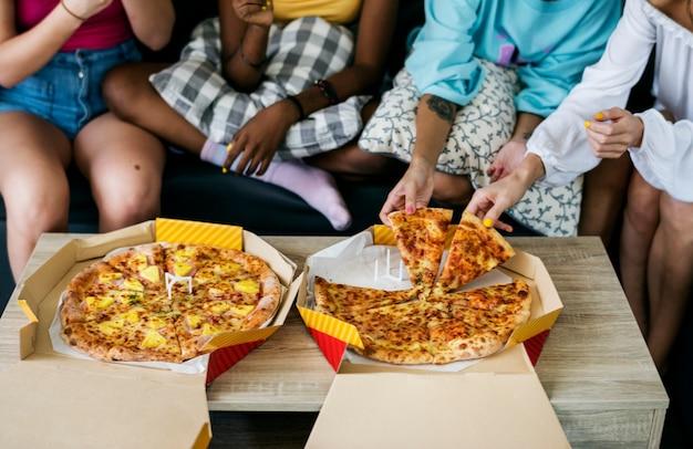 Разнообразные женщины сидят на диване, едят пиццу вместе Premium Фотографии