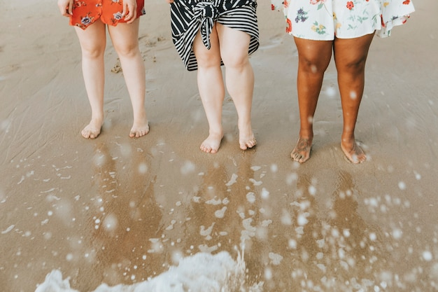 Diverse women soaking their feet in the water Free Photo
