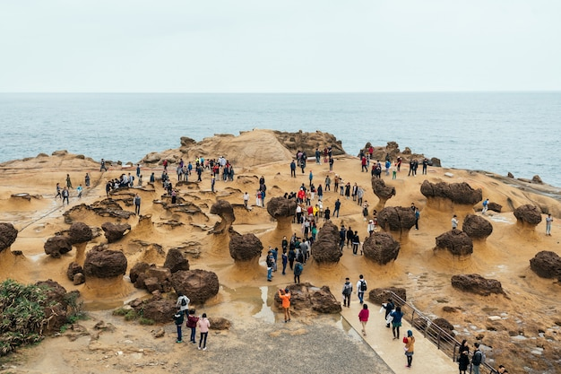 Diversity of tourists walking in yehliu geopark, a cape on the north coast of taiwan. Premium Photo