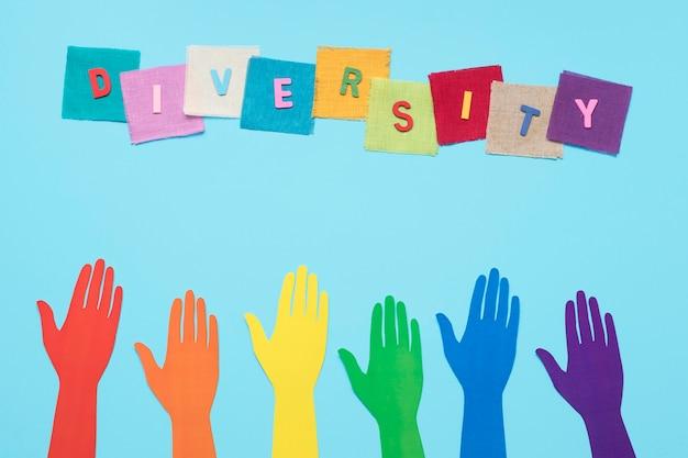 Parola di diversità fatta con carte colorate accanto a mani di carta colorata Foto Gratuite