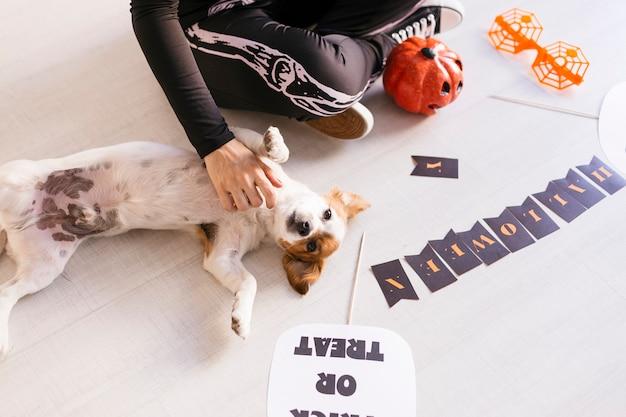 Молодая женщина делает хэллоуин гирлянды. творческий diy. домашний декор проект партии. хэллоуин ремесло вдохновения. cuet маленькая собака, кроме Premium Фотографии