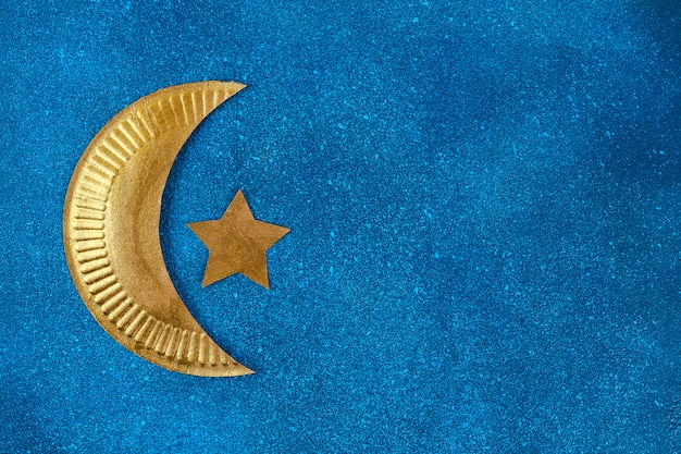 Diy ramadan kareem crescent moon with a star from a disposable cardboard plate and gold paint. Premium Photo