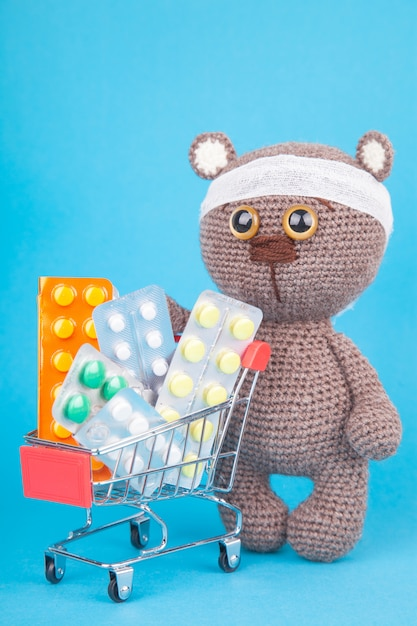 Diy toy. knitted brown bear.  shopping for medicines, healthcare costs and prescription medication concept with a shopping trolley filled with pills Premium Photo