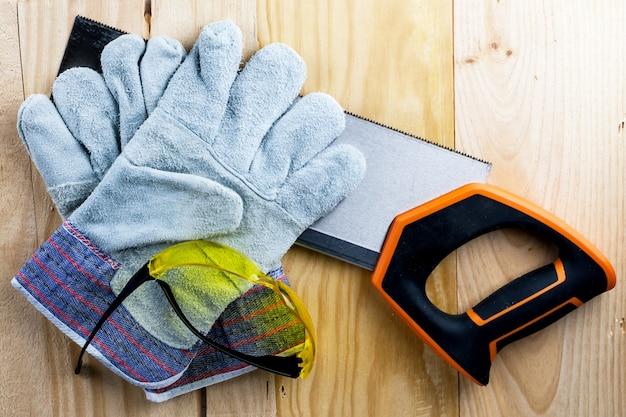 家の建設や修理に取り組みます。独立した更新、改修。のこぎり、作業用手袋、巻尺、ゴーグルを使用します。 diy、職場の安全、労働者保護のコンセプト Premium写真