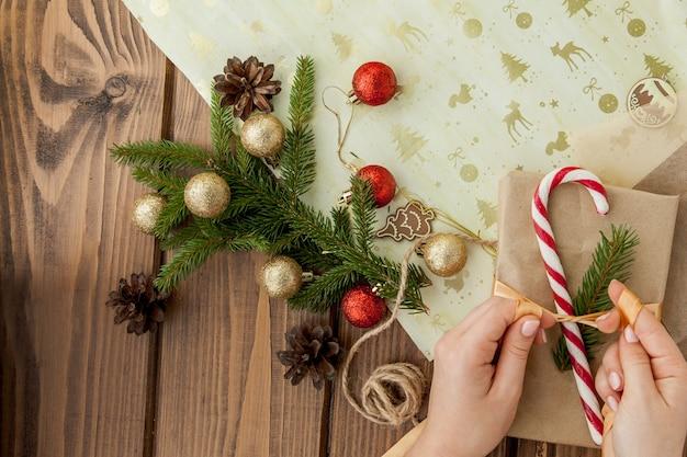 クリスマスプレゼントを包む女性の手をクローズアップ。準備ができていないクリスマスプレゼントの木製の装飾要素とアイテム、トップビュー。クリスマスまたは新年のdiyパッキング。 Premium写真