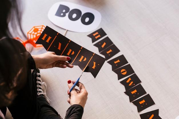 Молодая женщина делает хэллоуин гирлянды. творческий diy. домашний декор проект партии. хэллоуин ремесло вдохновения. Premium Фотографии