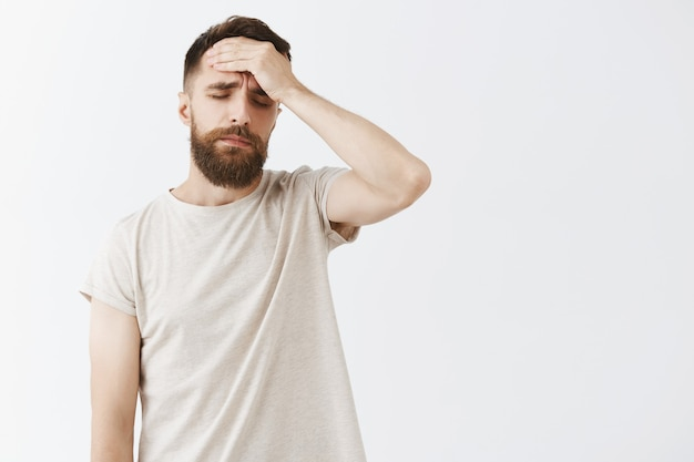 Dizzy bearded man posing against the white wall Free Photo