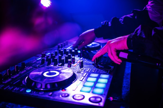 Dj console for mixing music with hands and with blurred people dancing at a night club party Premium Photo