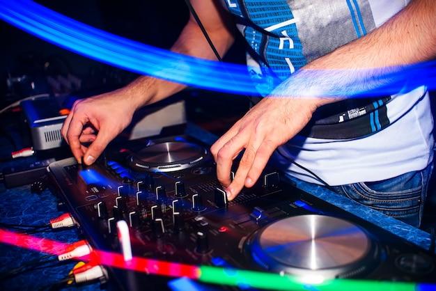 規制当局の手がナイトクラブのdj機器でdj音楽をひねる Premium写真